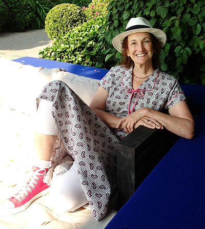 Photo of Sonya Sones kicking back on a porch in a blue folksy dress, red high-top sneakers, and a Panama hat from her webpage